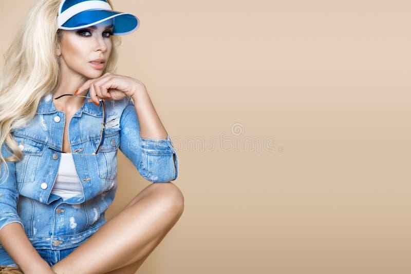 Mooi blonde vrouwelijk model die een denimjasje en borrels dragen stock afbeeldingen