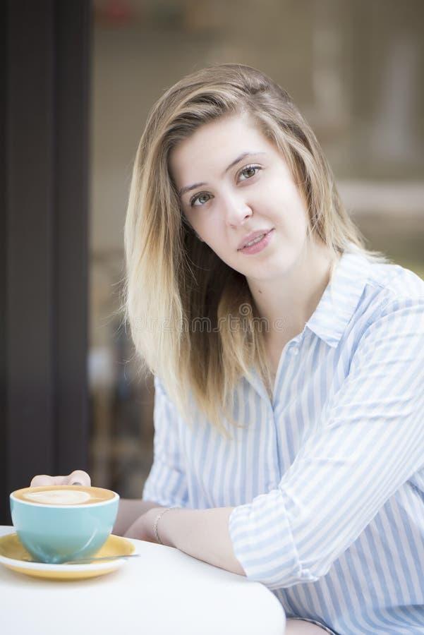 Mooi blondemeisje bij een lijst in een koffie met een kop van koffie stock afbeelding