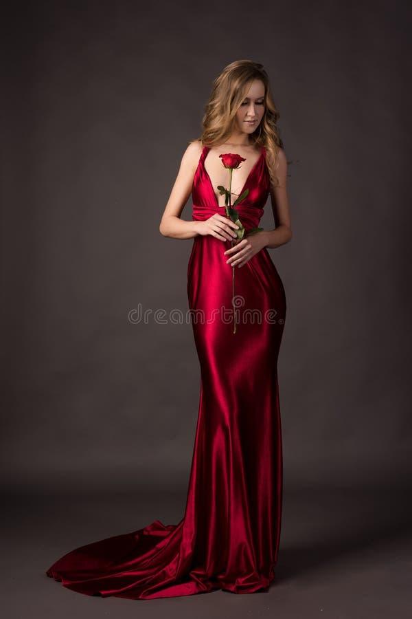 Mooi blondemeisje die een diepe kleding van het halslijn rode satijn ho dragen royalty-vrije stock foto