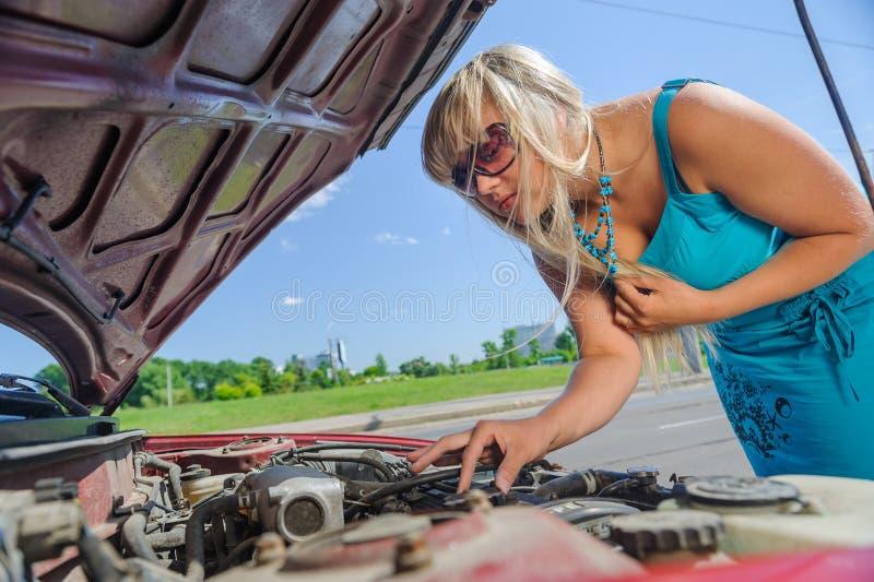 Mooi blondemeisje die onder de kap van de auto kijken stock fotografie