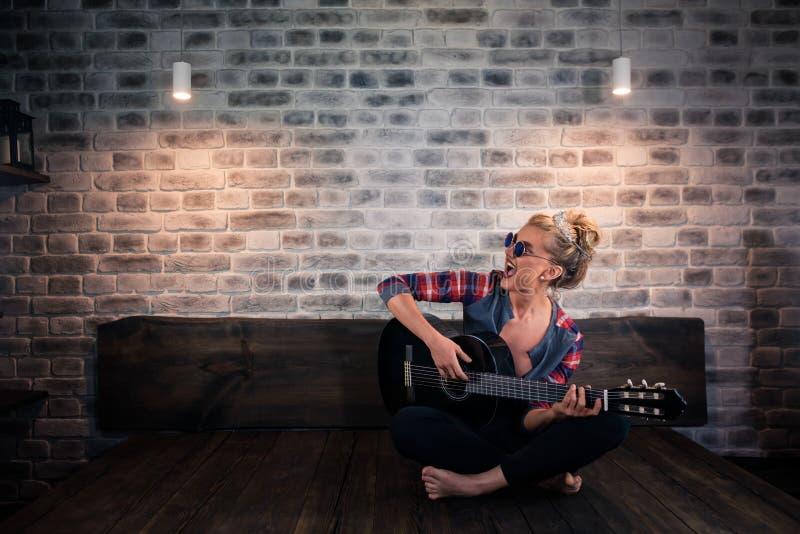 Mooi blondemeisje die in oorzakelijke kleren muziek bij gitaar en het zingen spelen royalty-vrije stock foto's