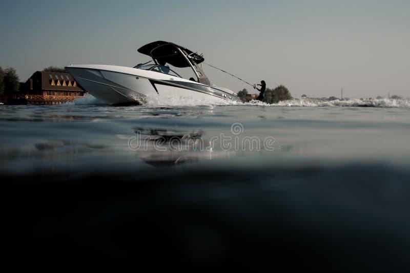 Mooi blondemeisje die op wakeboard berijden die een kabel op de motorboot houden royalty-vrije stock foto's
