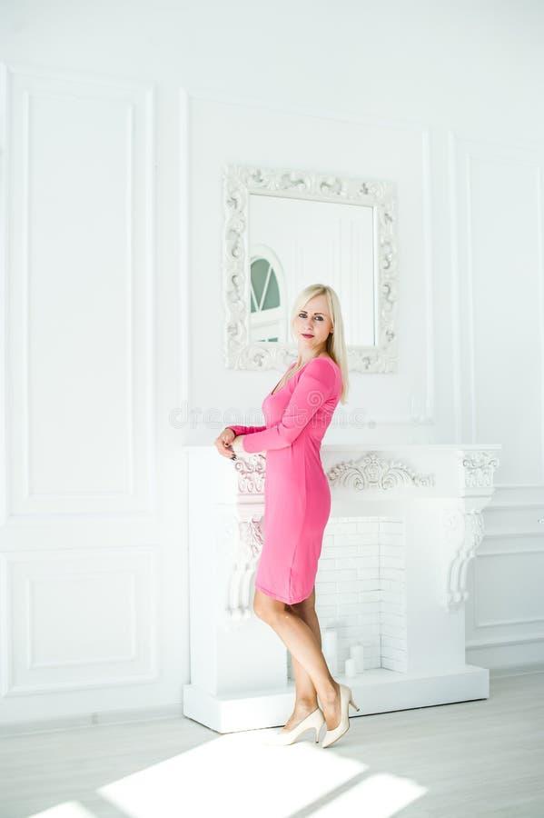 Mooi blondemeisje die zich dichtbij grote spiegel in witte studio bevinden stock foto's