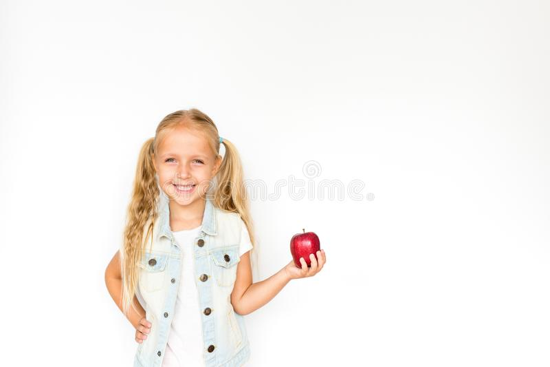 Mooi blondemeisje die zich op witte achtergrond bevinden en verse rode appel houden Gezond voedselconcept stock afbeelding