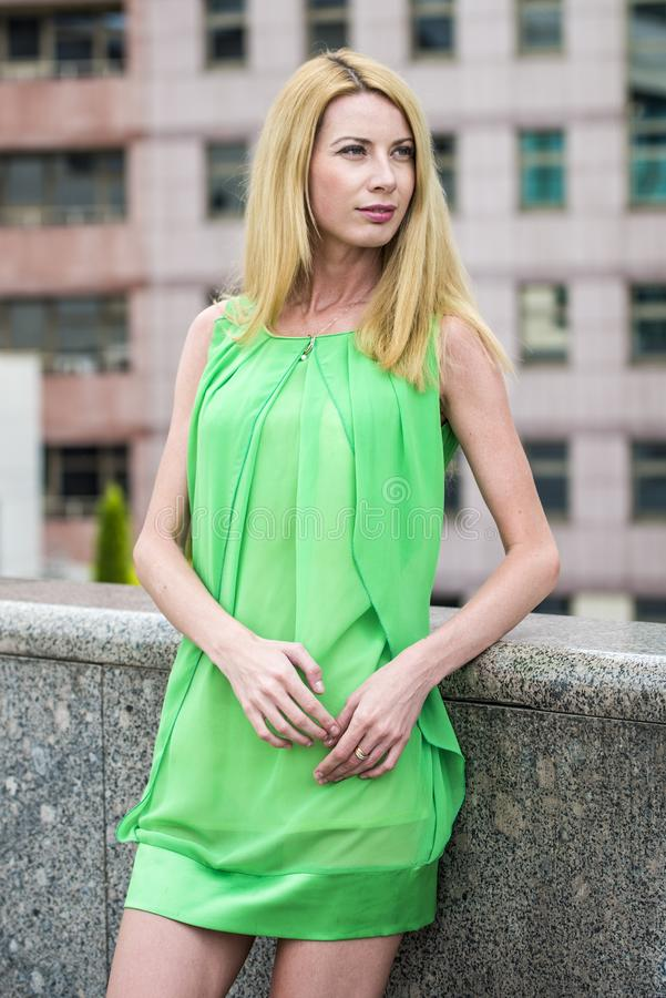 Mooi blondemeisje in een groene korte de zomerkleding op de straten van de stad stock afbeelding