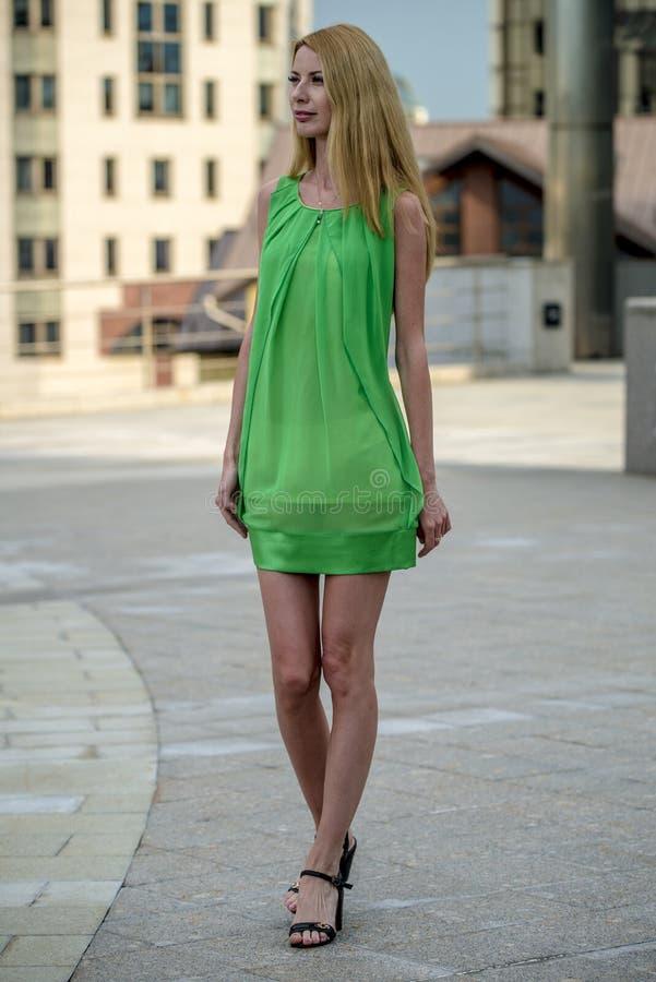 Mooi blondemeisje in een groene korte de zomerkleding op de straten van de stad stock foto's