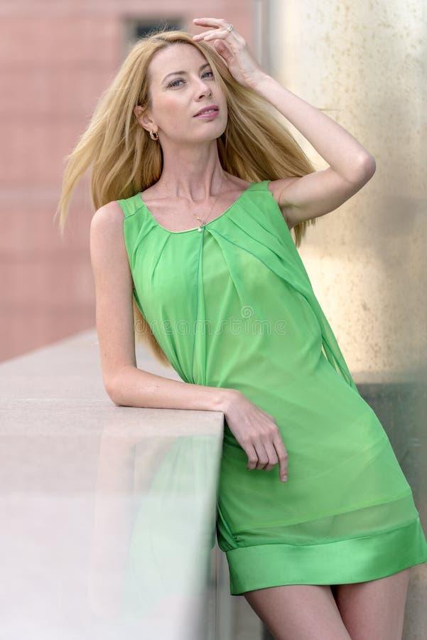 Mooi blondemeisje in een groene korte de zomerkleding op de straten van de stad stock foto