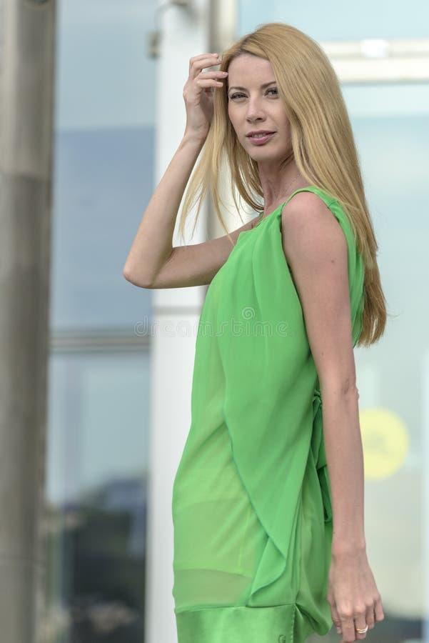 Mooi blondemeisje in een groene korte de zomerkleding op de straten van de stad royalty-vrije stock afbeelding