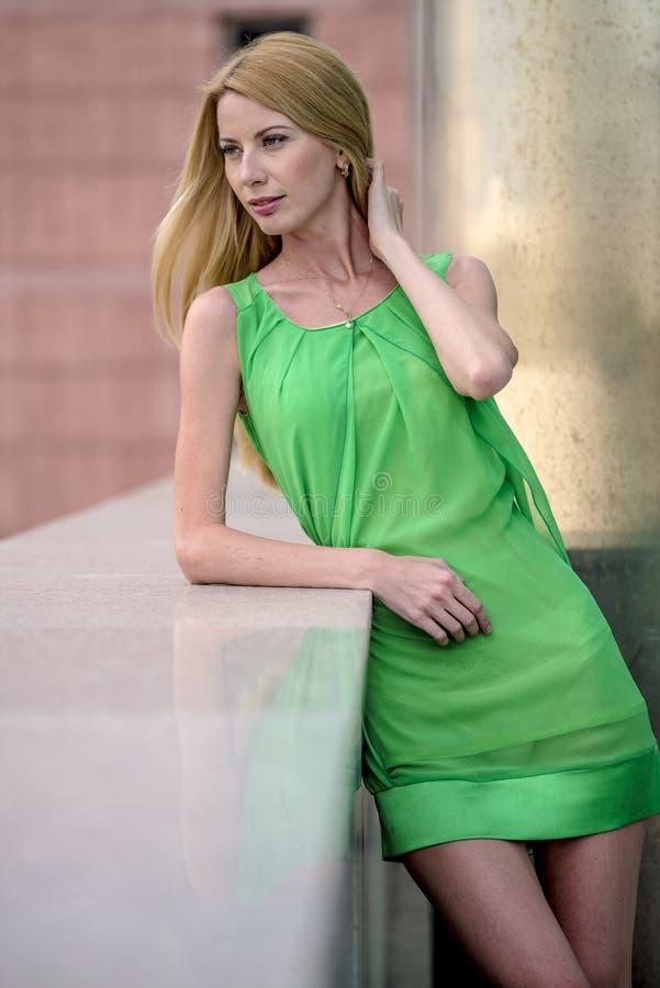 Mooi blondemeisje in een groene korte de zomerkleding op de straten van de stad stock fotografie