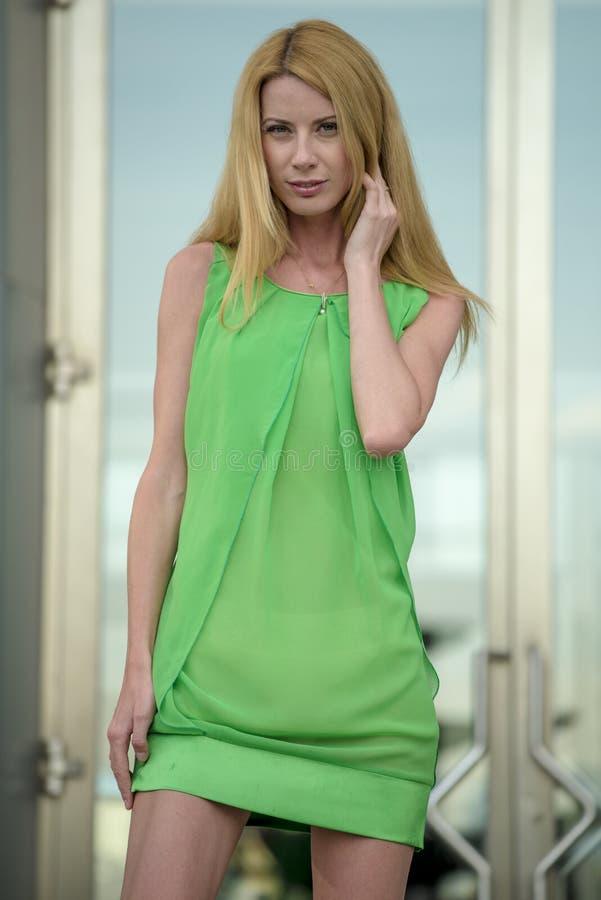 Mooi blondemeisje in een groene korte de zomerkleding op de straten van de stad royalty-vrije stock fotografie