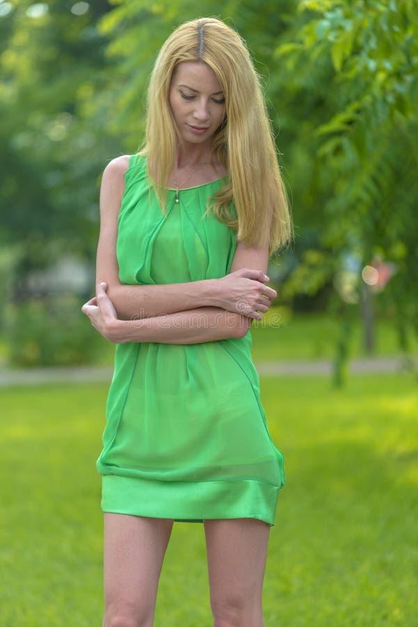 Mooi blondemeisje in een groene korte de zomerkleding op de straten van de stad royalty-vrije stock afbeeldingen