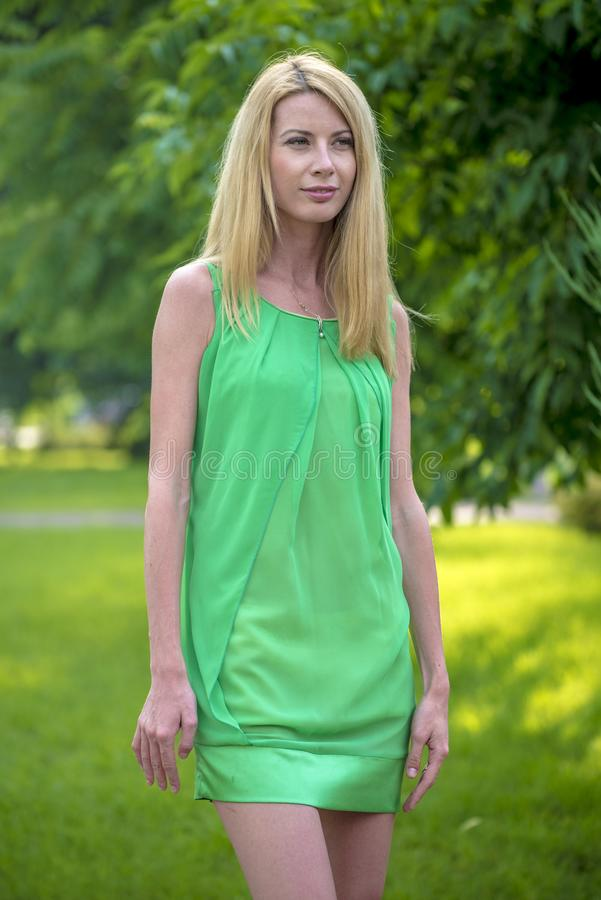 Mooi blondemeisje in een groene korte de zomerkleding op de straten van de stad royalty-vrije stock foto