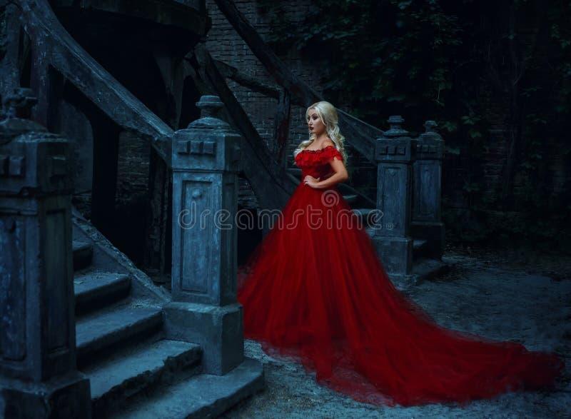 Mooi blondemeisje in een luxueuze rode kleding stock fotografie