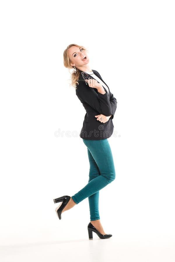 Mooi blondemeisje in een zwart jasje, een purpere broek en schoenen met hielen royalty-vrije stock afbeeldingen