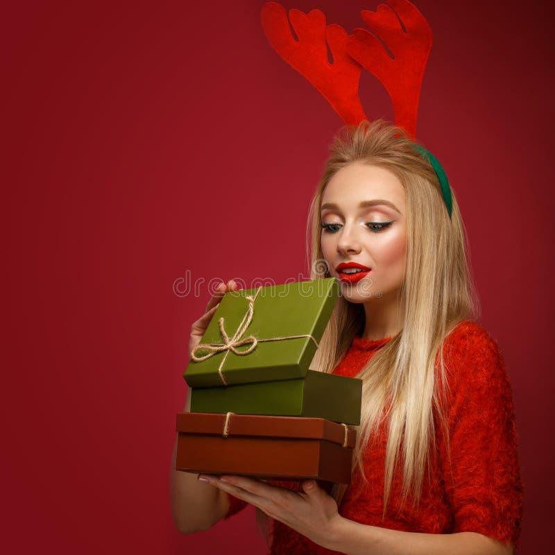 Mooi blondemeisje in het beeld van een Nieuwjaar met dozen van giften in handen en hertenhoornen op haar hoofd Schoonheidsgezicht stock afbeelding