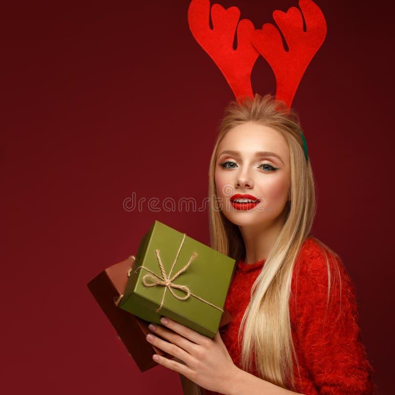 Mooi blondemeisje in het beeld van een Nieuwjaar met dozen van giften in handen en hertenhoornen op haar hoofd Schoonheidsgezicht royalty-vrije stock fotografie
