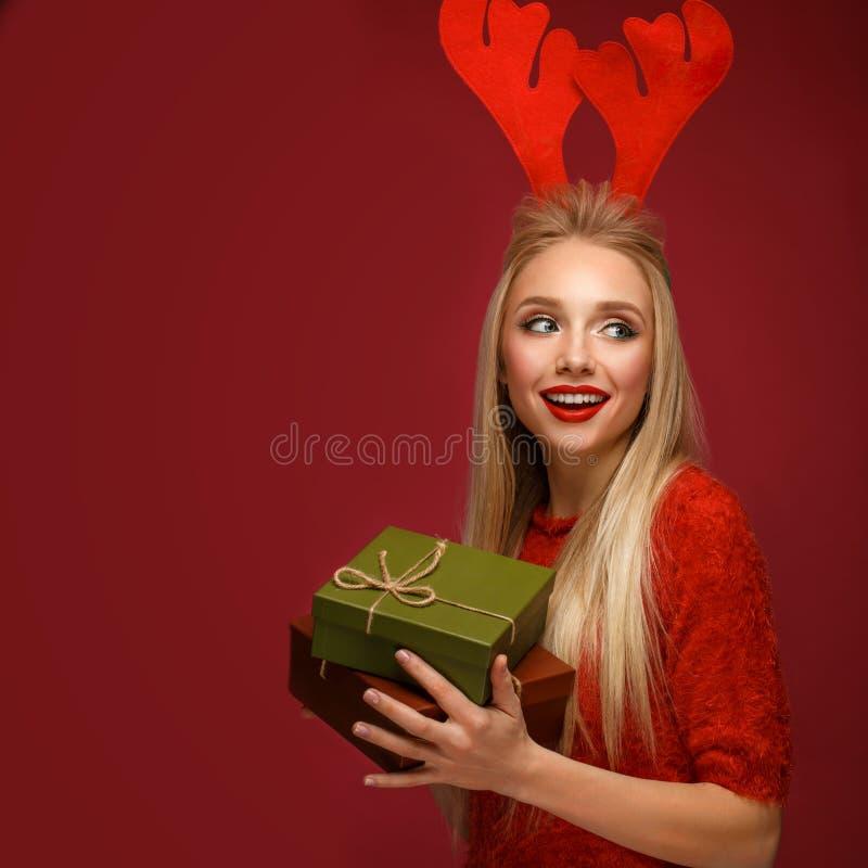 Mooi blondemeisje in het beeld van een Nieuwjaar met dozen van giften in handen en hertenhoornen op haar hoofd Schoonheidsgezicht royalty-vrije stock foto