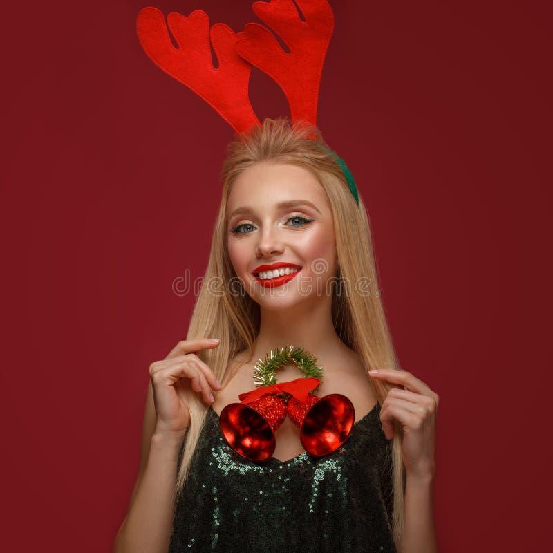 Mooi blondemeisje in het beeld van een Nieuwjaar met Kerstmisklokken rond haar hals en hertenhoornen op haar hoofd Het Gezicht va royalty-vrije stock afbeeldingen