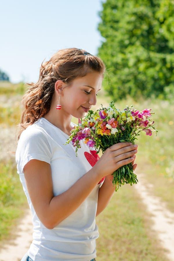 Mooi blondemeisje met een boeket van wilde bloemen in openlucht stock foto's