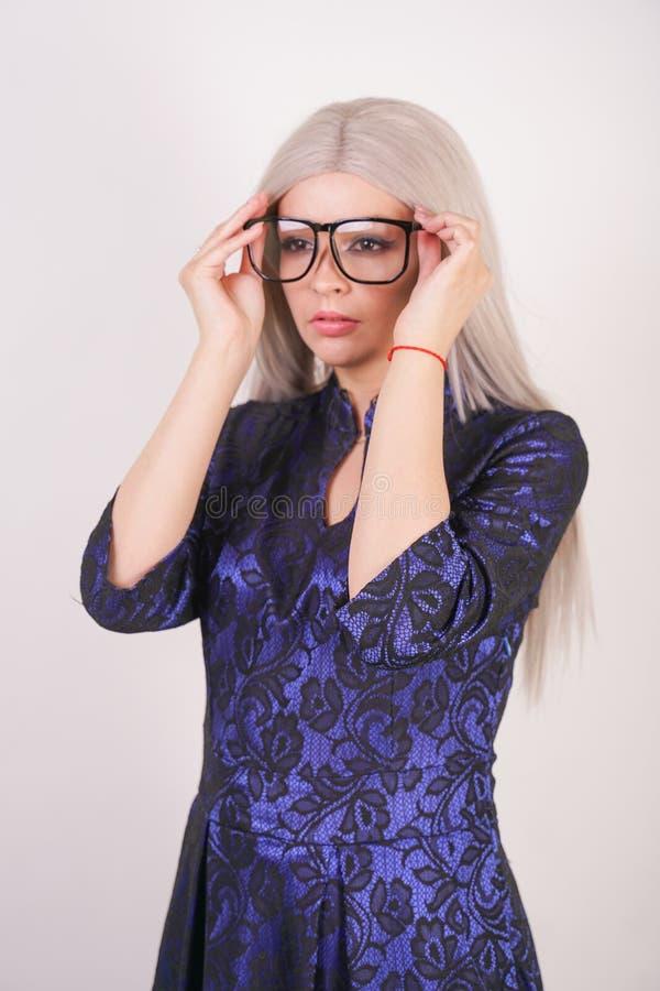 Mooi blondemeisje met glazen in luxueuze blauw met zwarte kantavondjurk op witte achtergrond in Studio stock afbeelding
