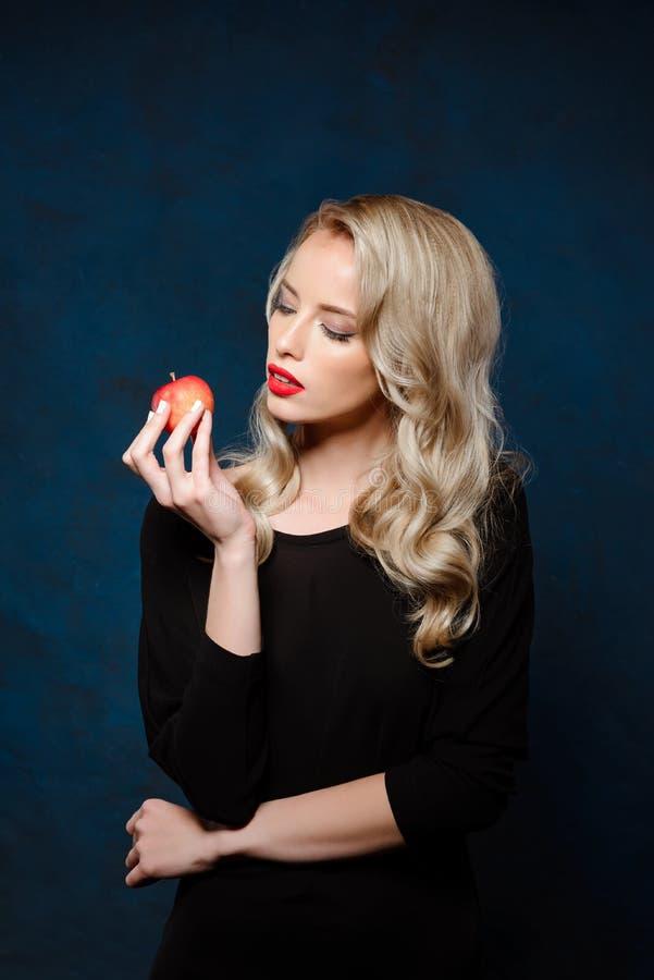 Mooi blondemeisje met heldere make-up in de zwarte appel van de kledingsholding stock foto