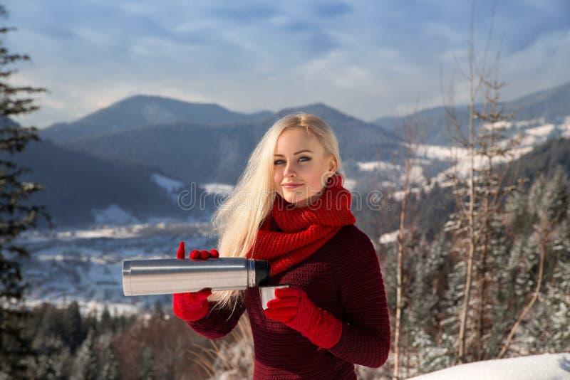 Mooi blondemeisje met hete drank in de winter stock fotografie