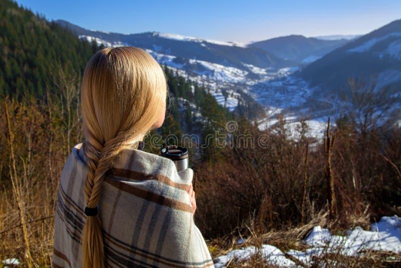 Mooi blondemeisje met hete drank in de winter stock afbeelding