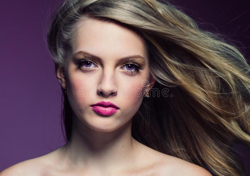 Mooi blondemeisje met lang krullend haar over purpere backgroun stock fotografie