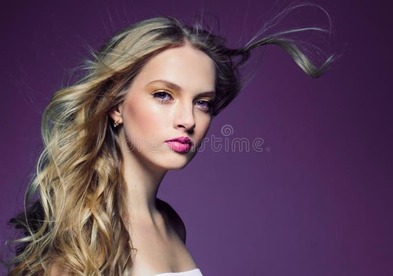 Mooi blondemeisje met lang krullend haar over purpere backgroun royalty-vrije stock afbeeldingen