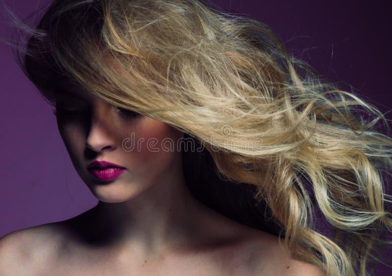 Mooi blondemeisje met lang krullend haar over purpere backgroun stock afbeeldingen