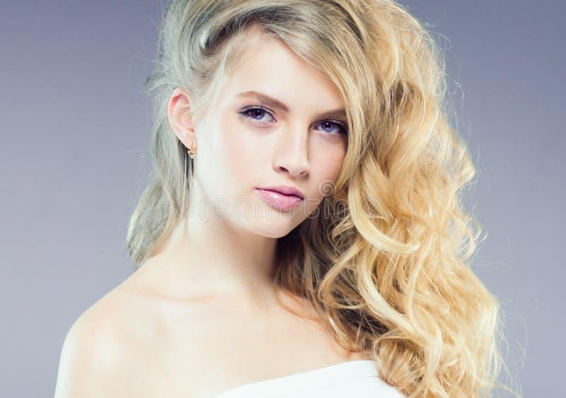 Mooi blondemeisje met lang krullend haar over purpere backgroun stock afbeelding