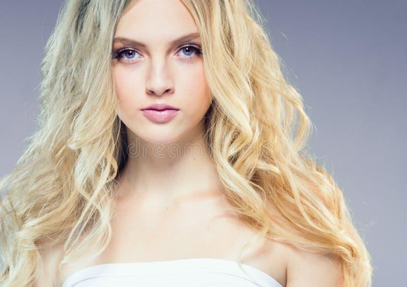 Mooi blondemeisje met lang krullend haar over purpere backgroun royalty-vrije stock foto's