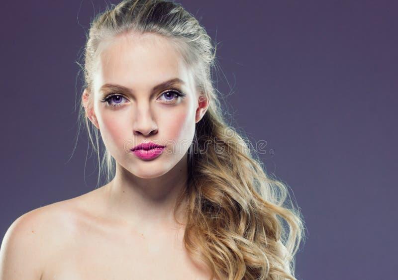 Mooi blondemeisje met lang krullend haar over purpere backgroun royalty-vrije stock foto