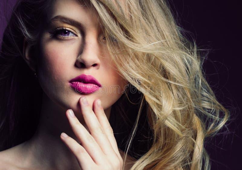 Mooi blondemeisje met lang krullend haar over purpere backgroun stock foto
