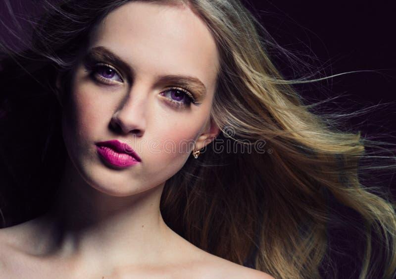 Mooi blondemeisje met lang krullend haar over purpere backgroun stock foto's