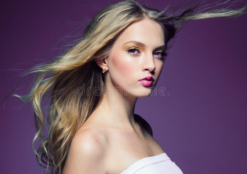 Mooi blondemeisje met lang krullend haar over purpere backgroun royalty-vrije stock afbeelding