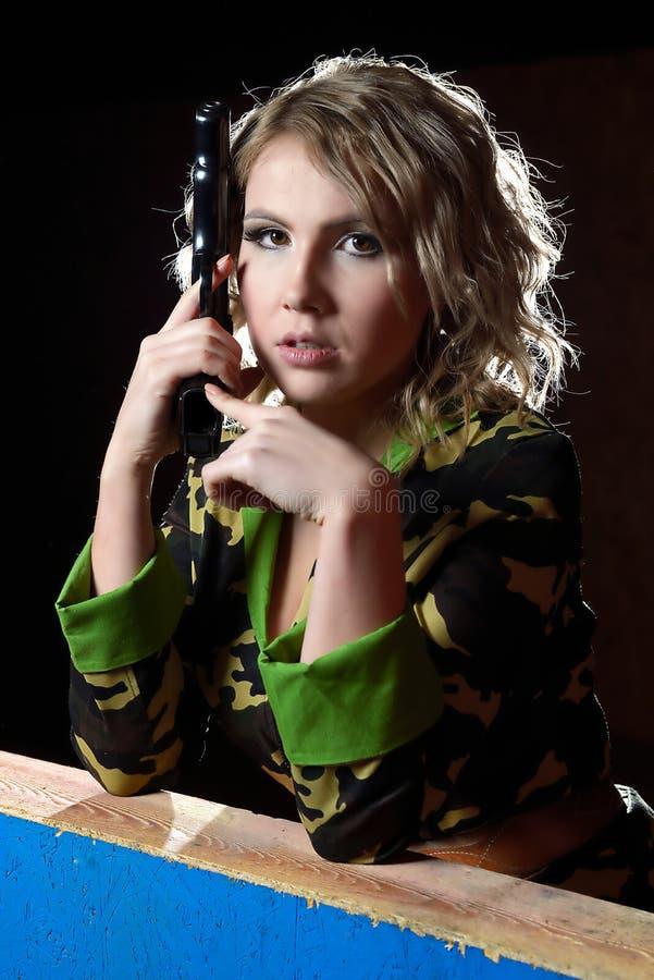 Mooi blondemeisje in militair kaki overhemd met kanon stock fotografie