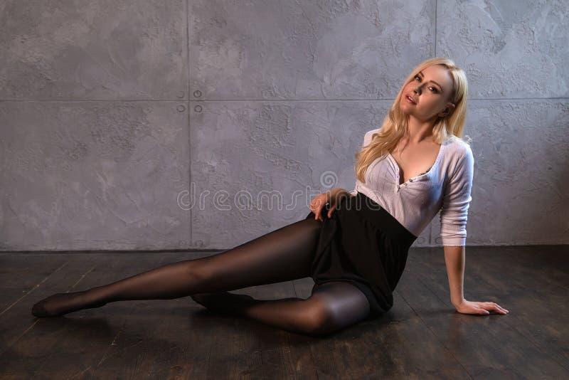 Mooi blondemeisje in nylonkousen het stellen op de vloer royalty-vrije stock foto
