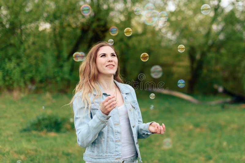 Mooi blondemeisje op aard in de zomer op een achtergrond van groene bomen met zeepbels 1 royalty-vrije stock foto's