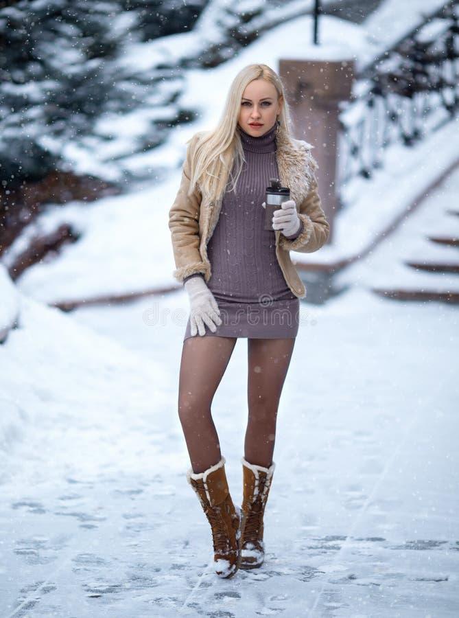 Mooi blondemeisje openlucht onder de harde sneeuw stock fotografie
