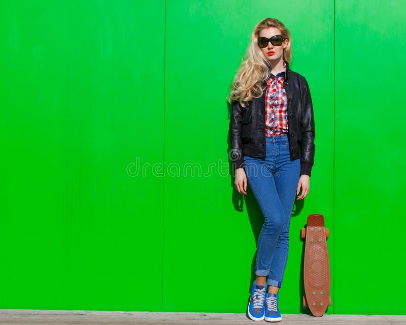 Mooi blondemeisje in reusachtige zonnebril en een zwart jasje die nex aan groene muur op een zonnige dag met een klein skateboard royalty-vrije stock foto's