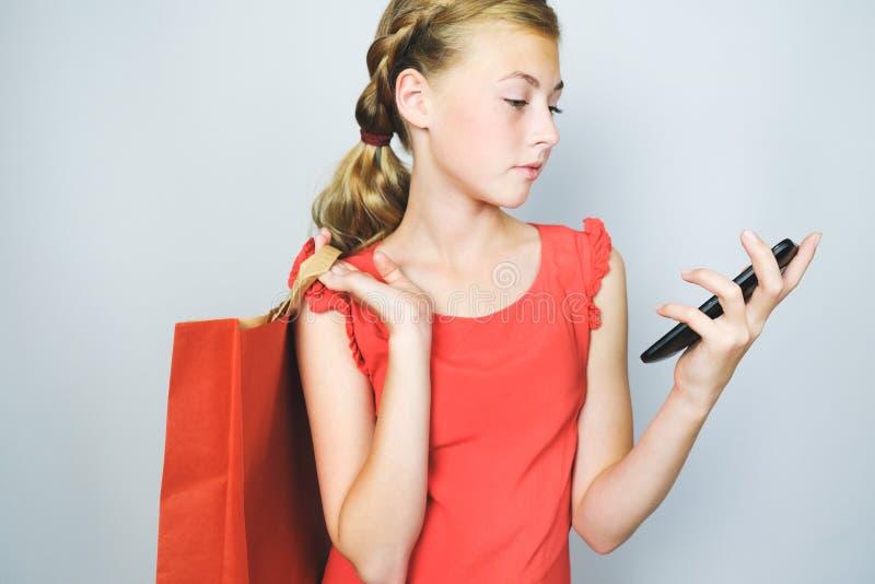 Mooi blondemeisje in rode kleding die cellphone bekijken en document het winkelen zak in haar hand houden royalty-vrije stock foto's