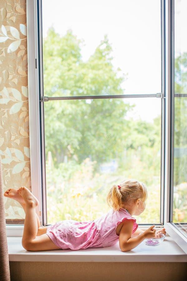 Mooi blondemeisje in roze kleding die dichtbij groot open venster op de vensterbank liggen thuis en met parels spelen royalty-vrije stock foto