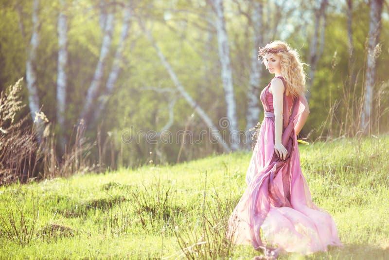 Mooi blondemeisje in roze lange kleding op een achtergrond van aard stock foto