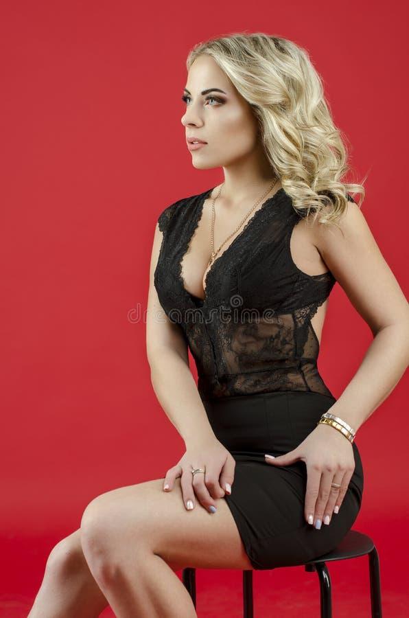 Mooi blondemeisje in zwarte kleding stock afbeelding