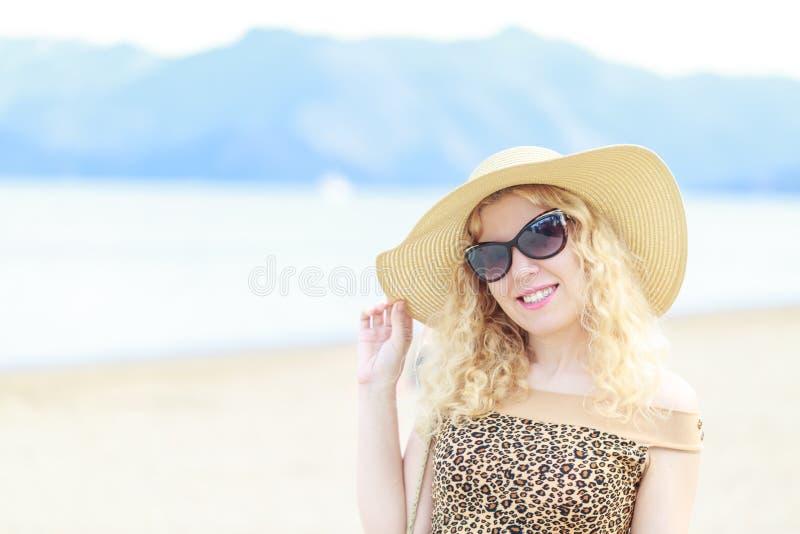 Mooi blondeportret op het strand met hoed en zonnebril royalty-vrije stock afbeelding