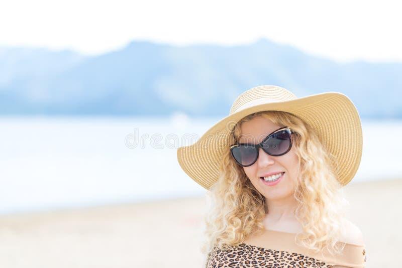 Mooi blondeportret op het strand met hoed en zonnebril stock foto's