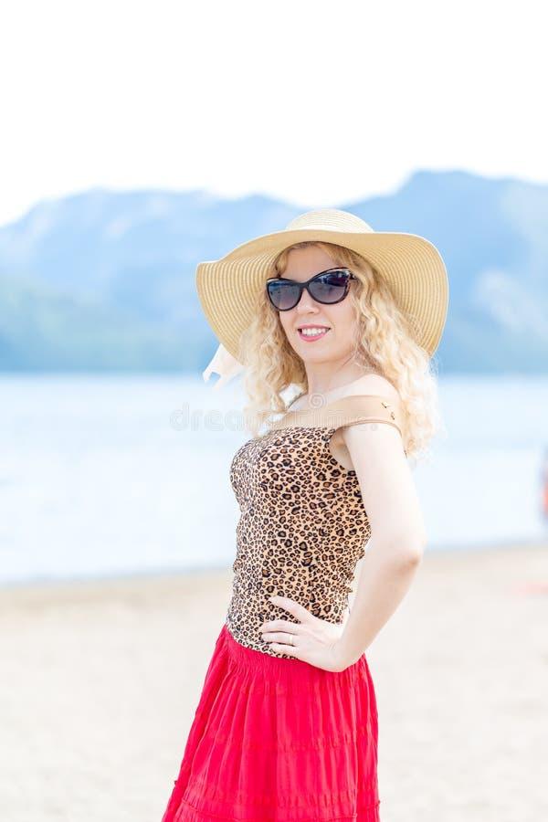 Mooi blondeportret op het strand met hoed en zonnebril royalty-vrije stock afbeeldingen