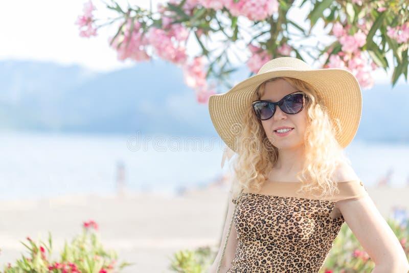 Mooi blondeportret op het strand met hoed en zonnebril royalty-vrije stock foto's