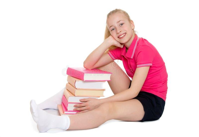 Mooi blondeschoolmeisje die een stapel koesteren van royalty-vrije stock foto